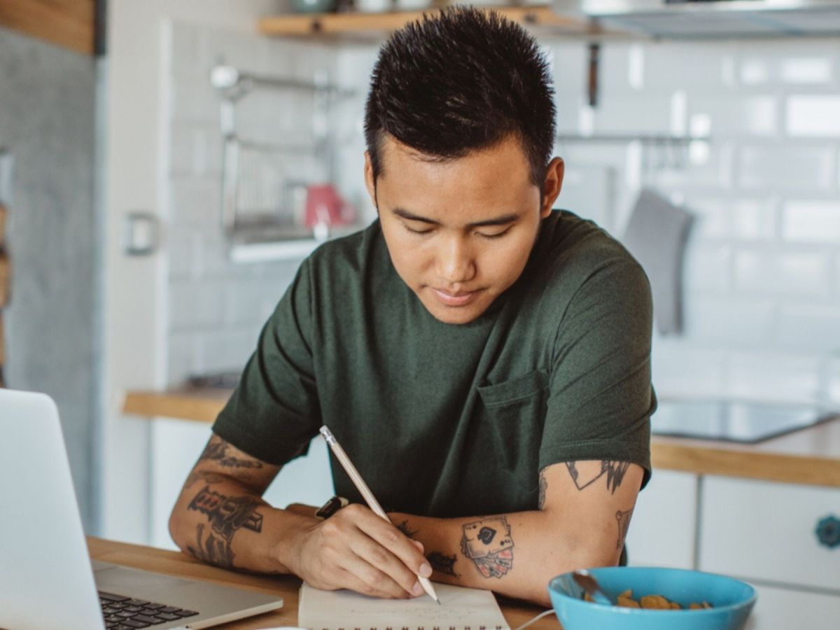 young man on computer leaning against kitchen island with bowl of cereal nearby