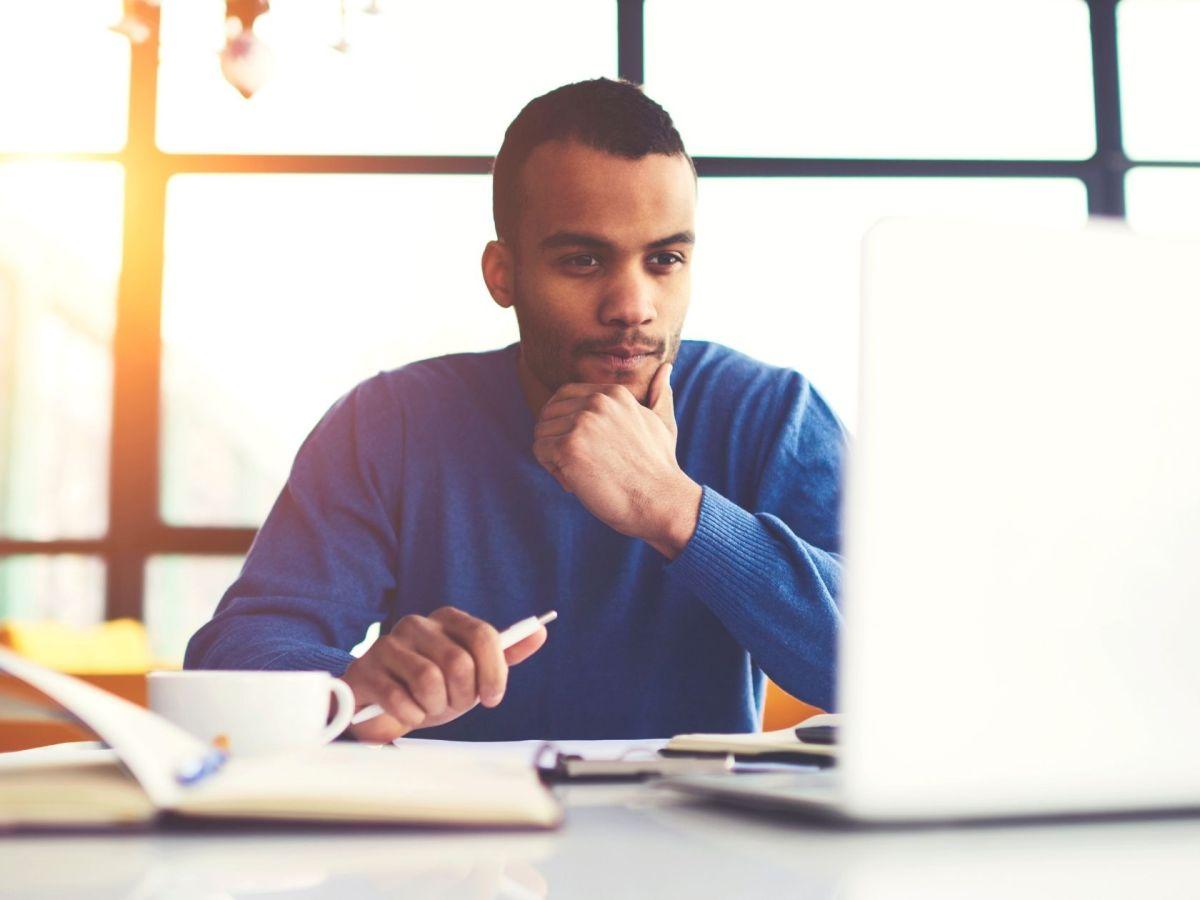 young man thinking looking at computer
