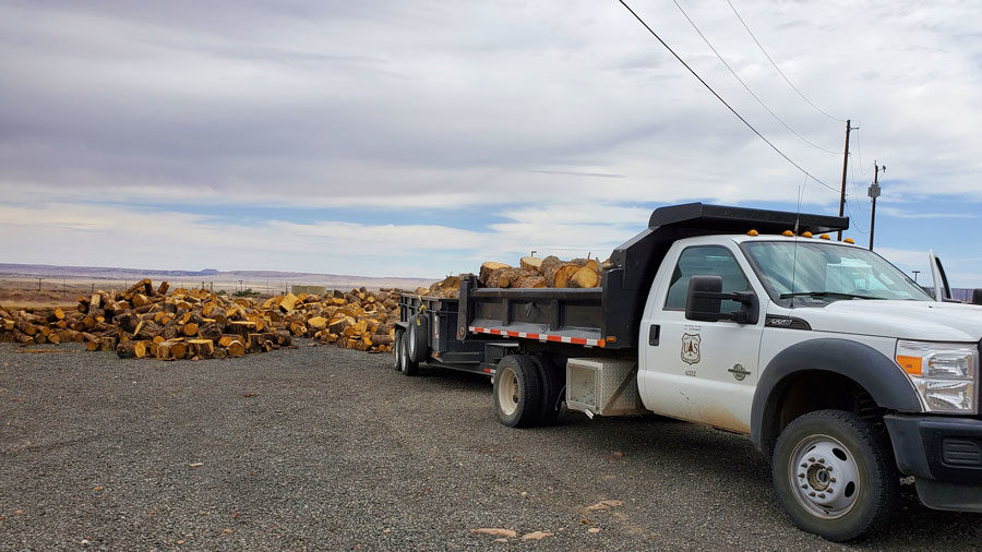 A white truck with the UDSA Forest Service shield on the door is pictured with a bed full of wood, ready for distribution.