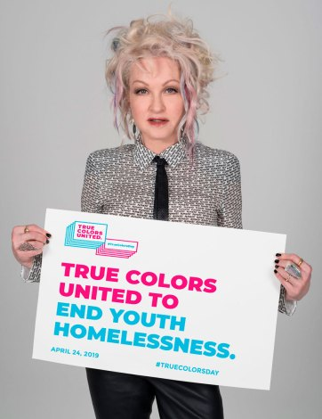 Cyndi Lauper holds a sign that says,