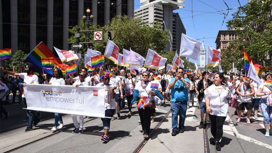 A large group of people march in a Pride parade carrying rainbow flags and a banner that says, 'You're empowerful.'