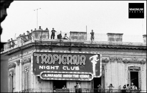 CUBA. La Havana. 1959. Bystanders on the roof of a building and balcony of a nightclub watch as rallies begin to form in the streets. ©BurtGlinn/Magnum