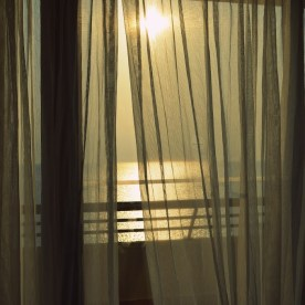 Curtains billowing in the wind of the Aegean