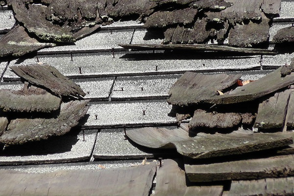 broken asphalt shingle roof in need of immediate replacement