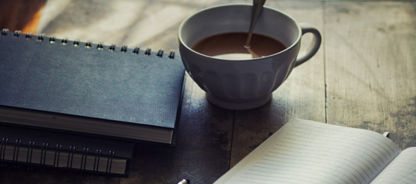 teacup and notebook on a brown desk.
