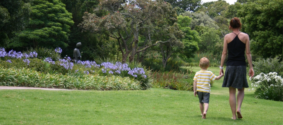 young child walkign with mother in beautiful garden