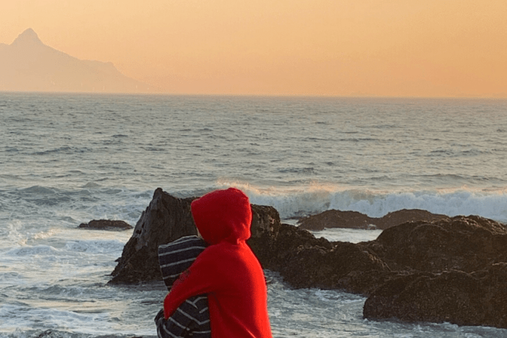 Brothers hugging on the beach, looking at the ocean and Table Mountain.