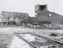 A brick warehouse destroyed near the railroad tracks.