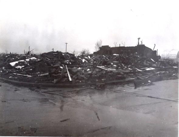 A demolished concrete block building housing a battery shop near downtown.