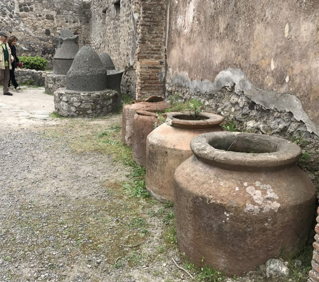 The containers or urns stored olive oil, which was used to light lamps at night. At the back is a good example of what the grain grinder looked on the inside.