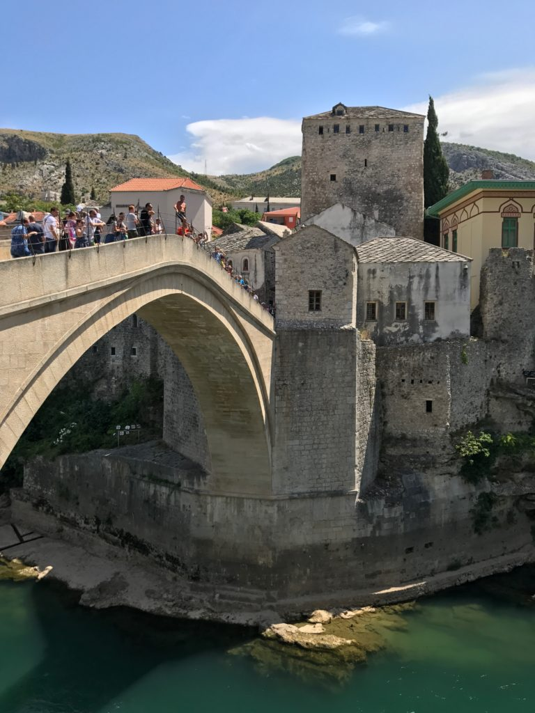 A guy getting ready to jump off the Stari Most in Mostar
