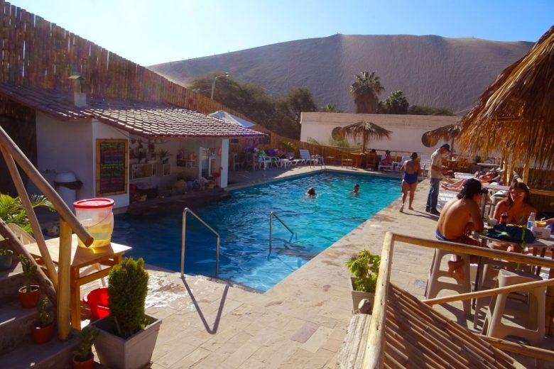 The pool and swim-up bar at Desert Nights Ecocamp comes with a great view of the surrounding sand dunes