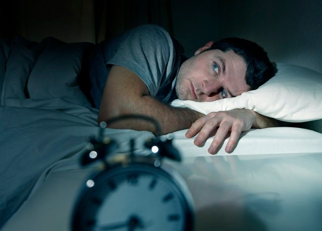 man in bed eyes opened suffering insomnia and sleep disorder