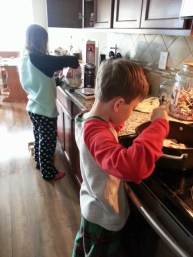 Sparkles prepping biscuits and Middle Boy frying bacon