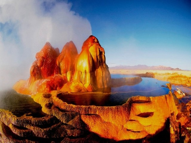 Shades of the World Series: Steam and water erupting out of Fly Geyser's orange, weird-looking mound, sided by a pool of water