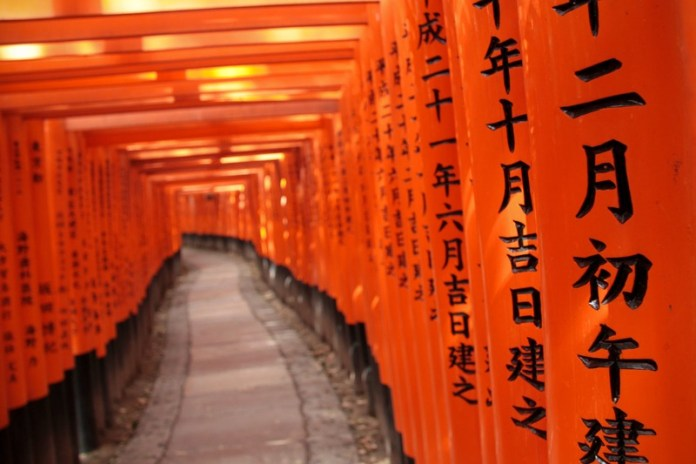 Shades of the World Series: The long walk leading to Fushimi Inari Shrine lined with thousands of orange Torii gates.