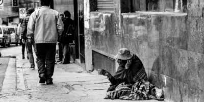 an old man sitting on sidewalk asking for help