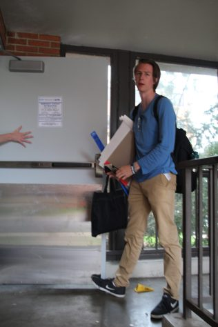 After using his card to gain access to AF, Sam Gersregen, a sophomore in the Graphics Design program, holds the door for his friends.