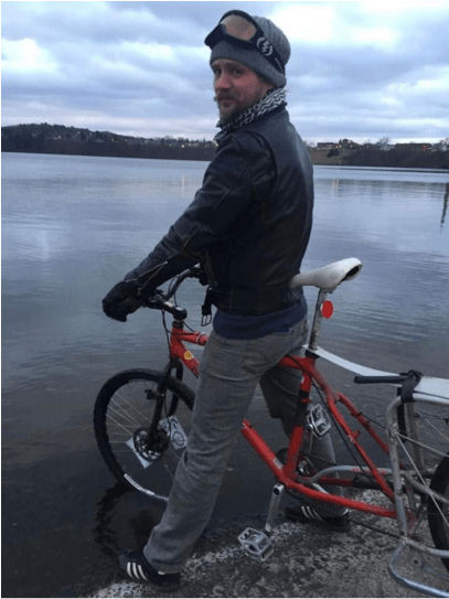 Kneeland with his bicycle on Lake Menomin.
