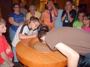 Micah dunks his head in the baptismal font