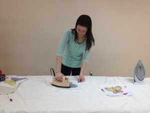 Hannah ironing a colored butterfly onto a fabric square.