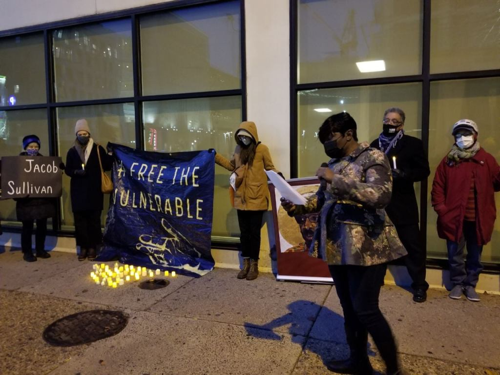 Pennsylvania candlelight vigil free incarcerated people during covid. Banner reads #Free The Vulnerable