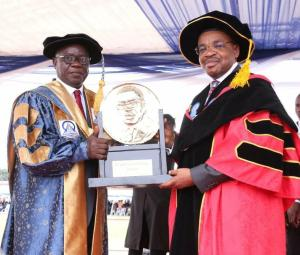 Umobong presenting a plaque to Emmanuel