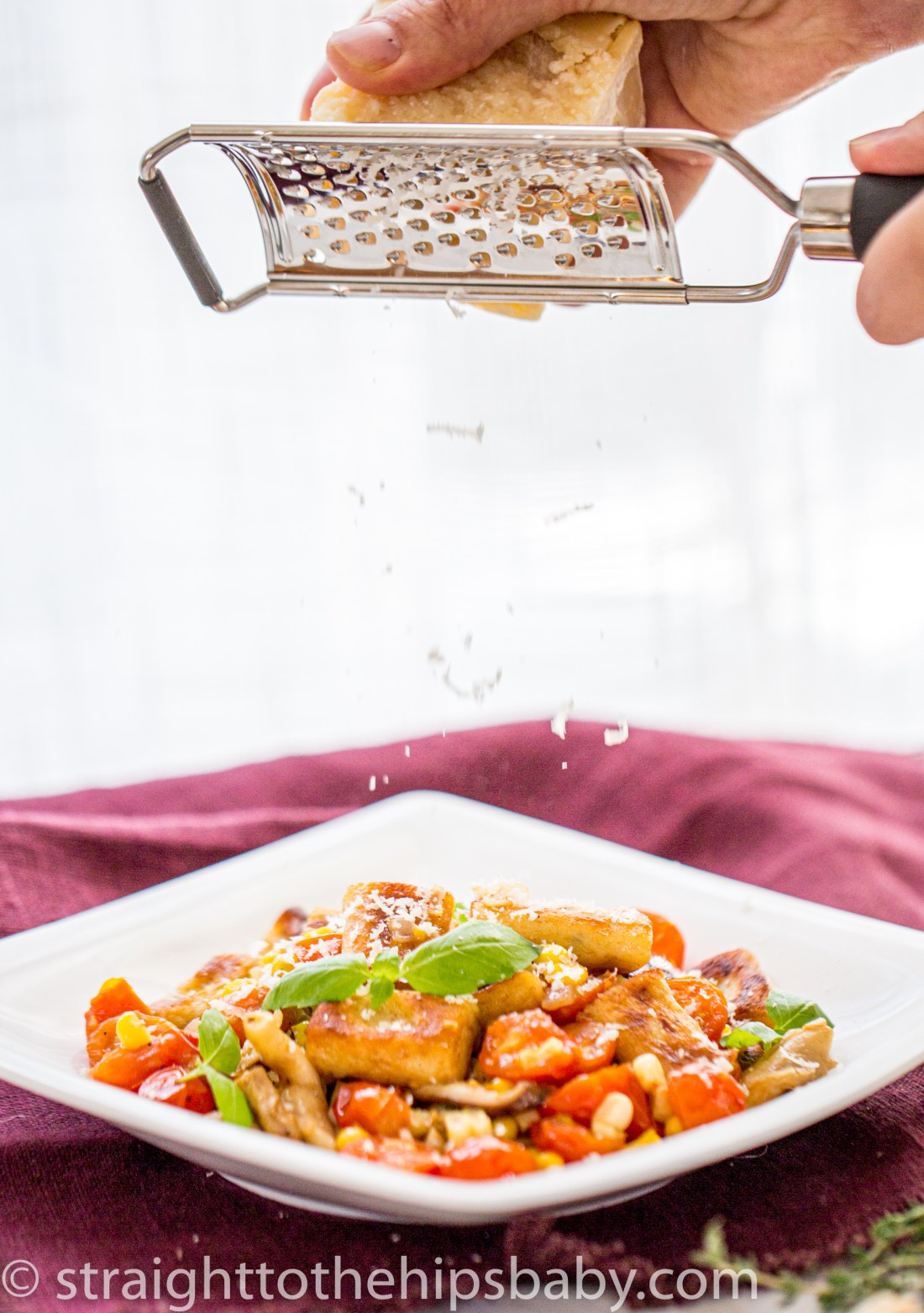grating fresh parmesan cheese over a plate of colorful fresh potato gnocchi with late summer vegetables