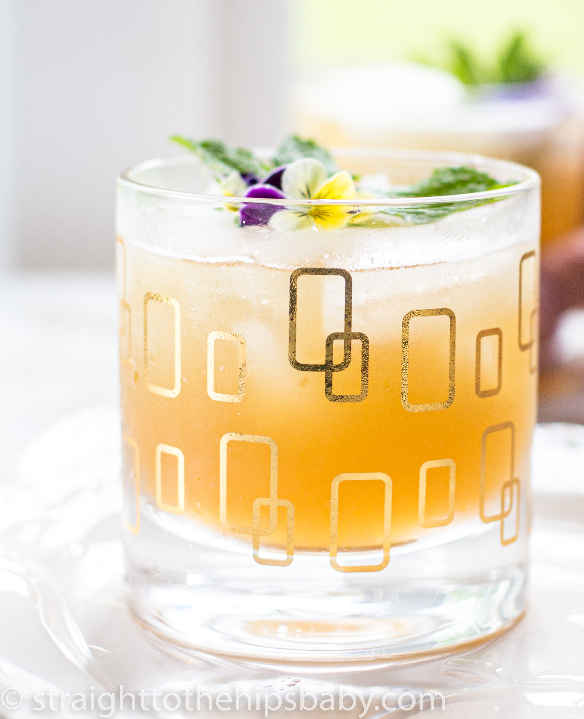 a chilled cocktail glass filled with whisky lemonade and garnished with flowers and mint