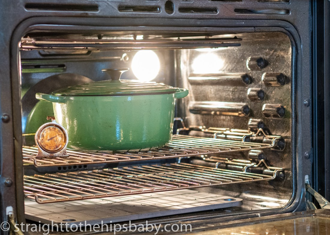 a heated oven with a large green cast iron pot heating for baking