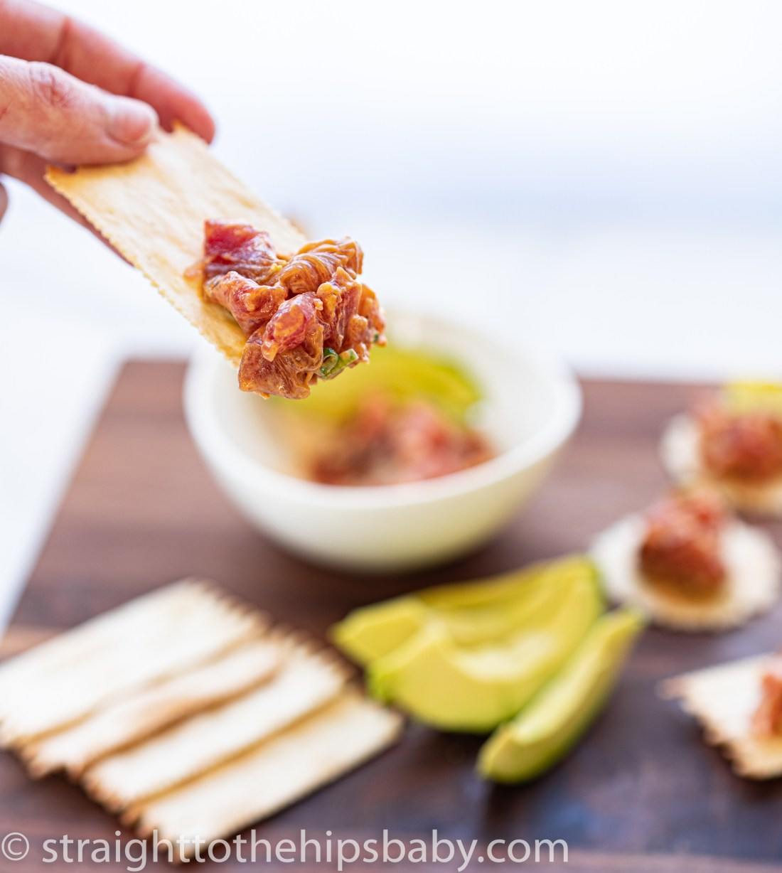 a woman's hand in the foreground, holding a cracker filled with tuna tartare. In the background, a blurred appetizer board with the same recipe