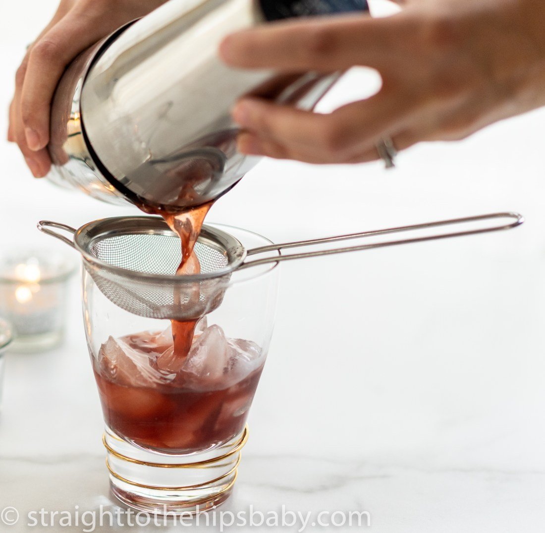 straining the dark magic margarita into a cocktail glass