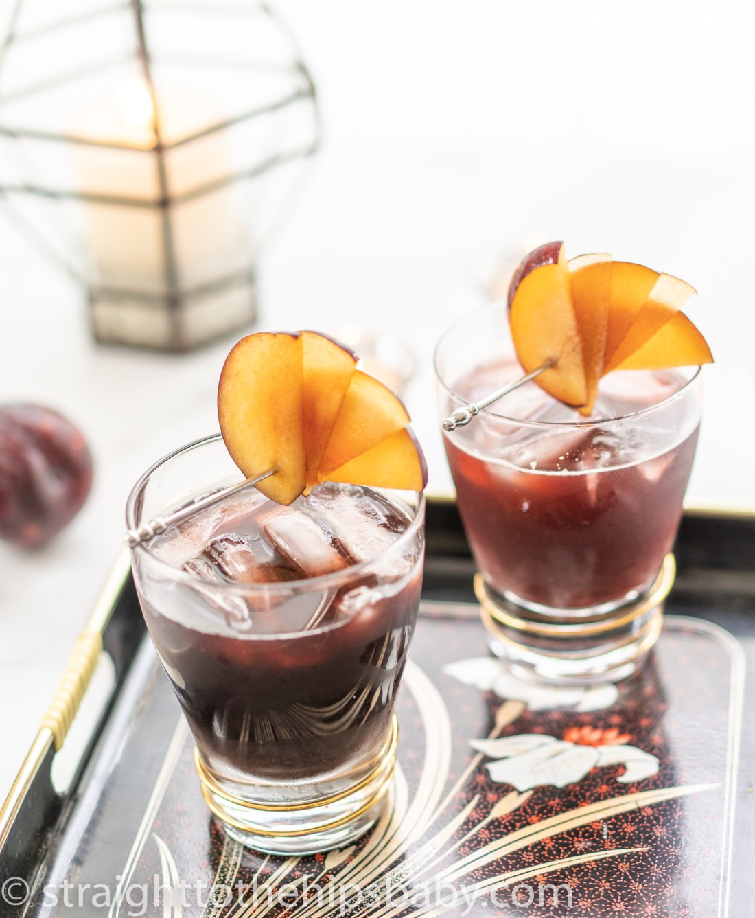 two cocktails with a plum garnish
