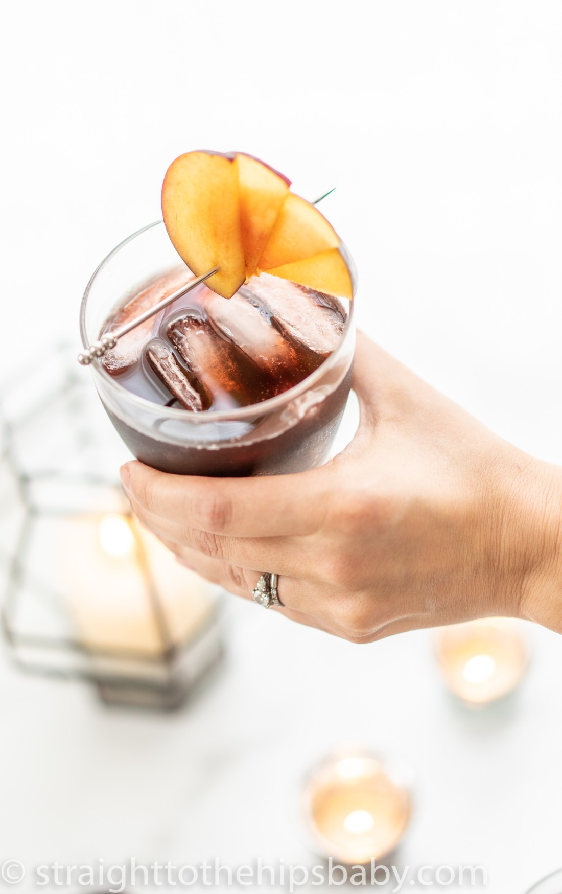 a woman's hand holding a finished ruby colored plum margarita