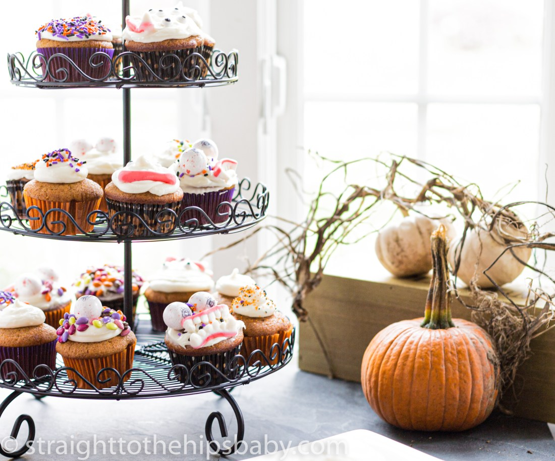 Black tiered wire cupcake stand filled with halloween decorated pumpkin spice cupcakes, with pumpkins in the foreground