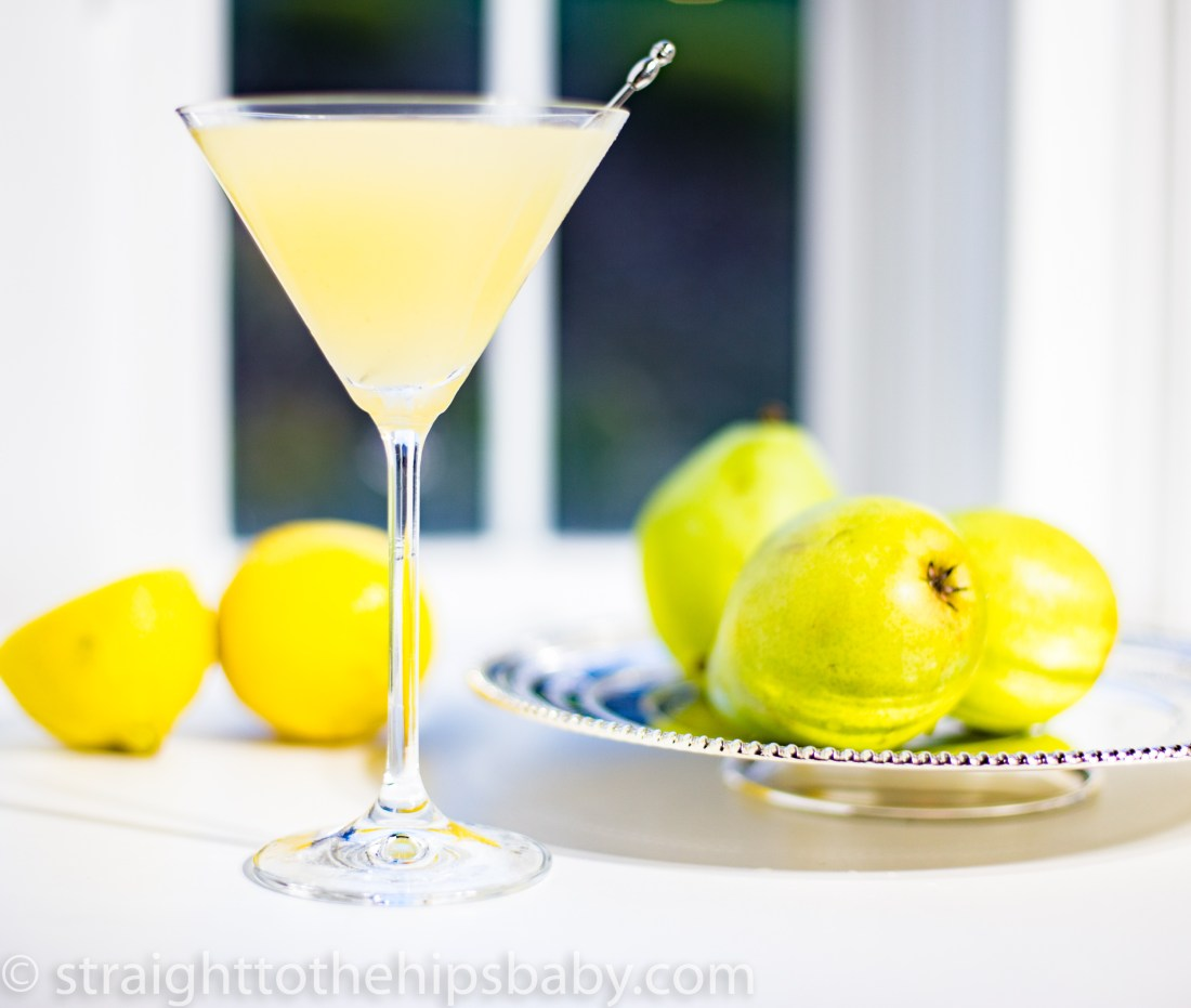 a chilled martini glass filled with light green Pear Vodka Cocktail, garnished with a silver cocktail stick