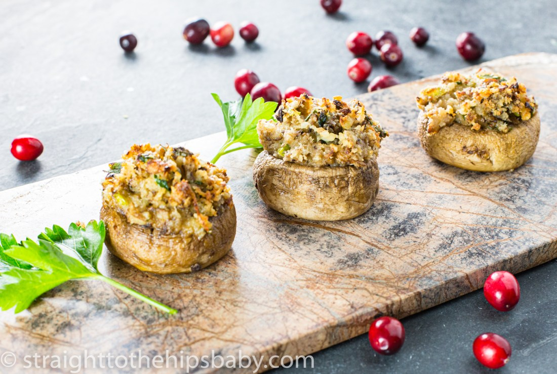 Three stuffed mushrooms on a stone serving board, with cranberries scatter in the background