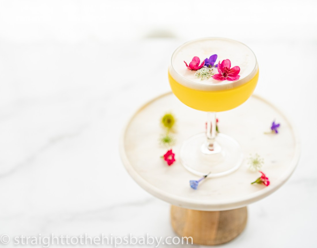 a finished lemon flora gin sour, pale yellow with a white egg foam. Garnished with fresh flowers.