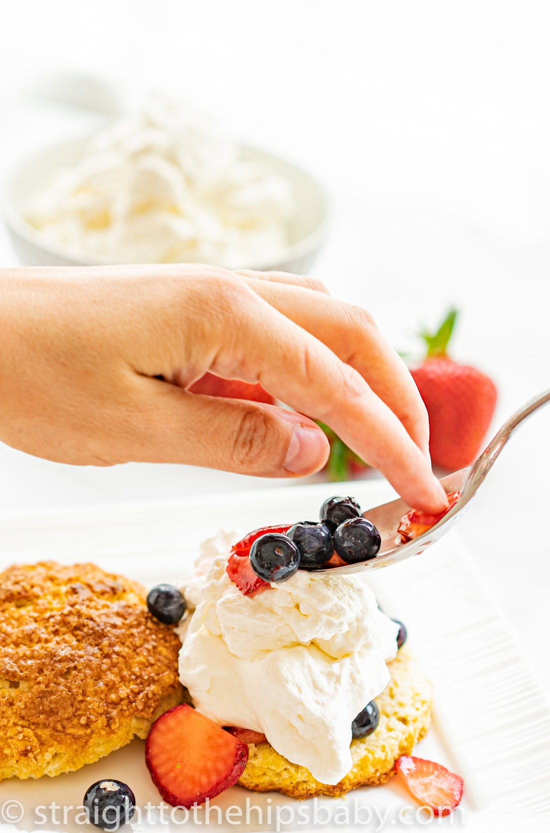 a woman's hand guiding sugared berries onto of a whipped cream coated biscuit