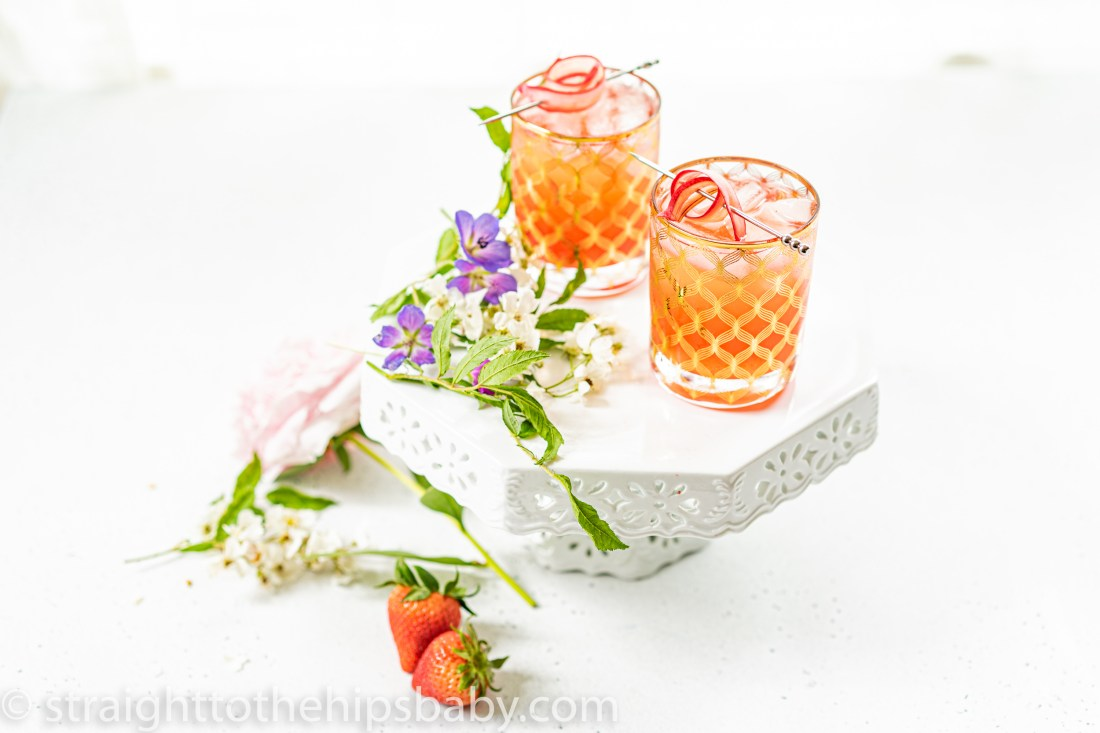 two orange pink rhubarb shrub cocktails, sitting on a white background with flowers