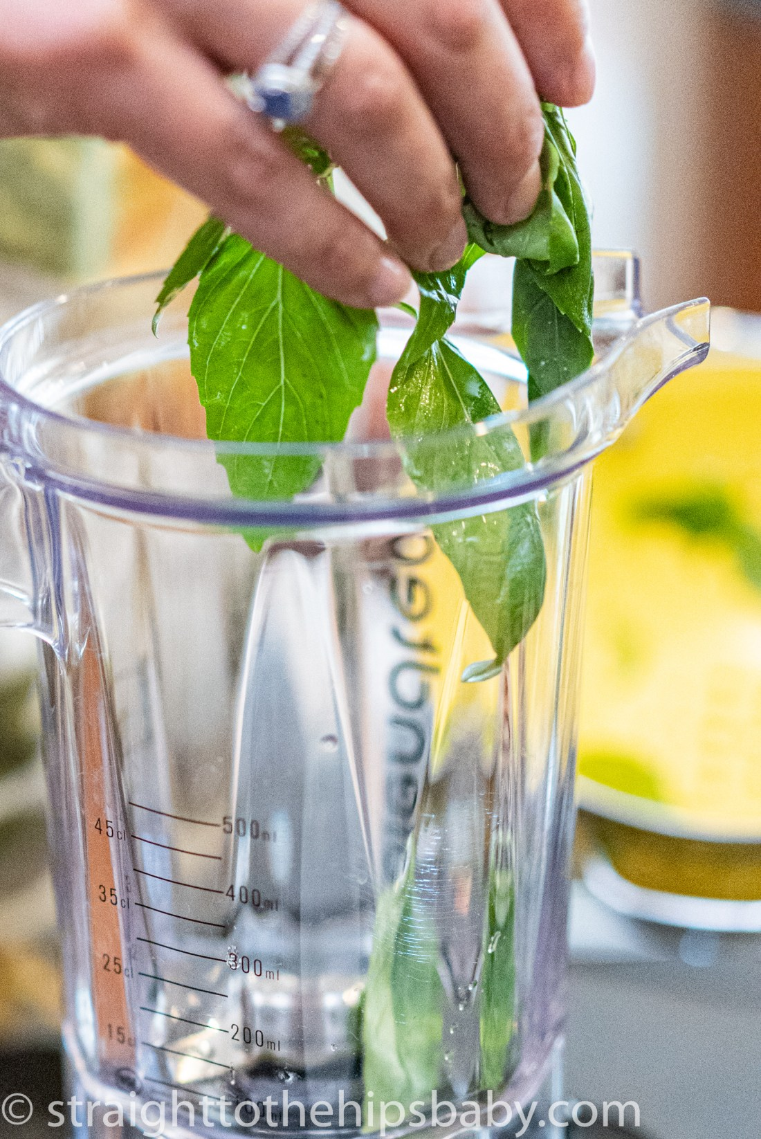 placing basil leaves into a blend for the creamy basil dressing