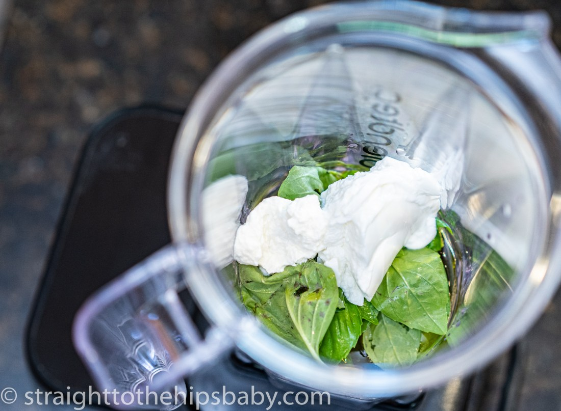 top down view of a blender with yogurt and basil leaves ready to be blended