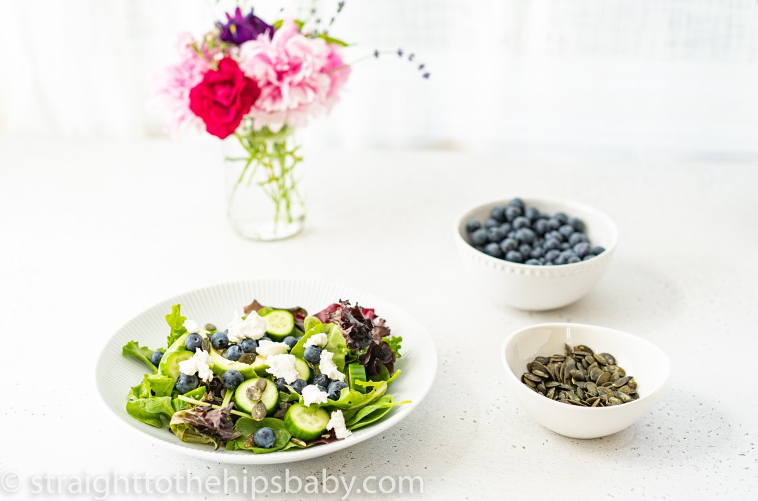 a bowl of undressed salad with bowls of sunflower seeds, blueberries, and pink flowers in the background
