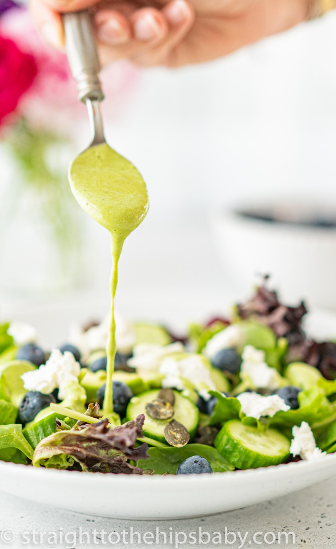 spooning a heaping portion of creamy green basil dressing onto a plate of salad