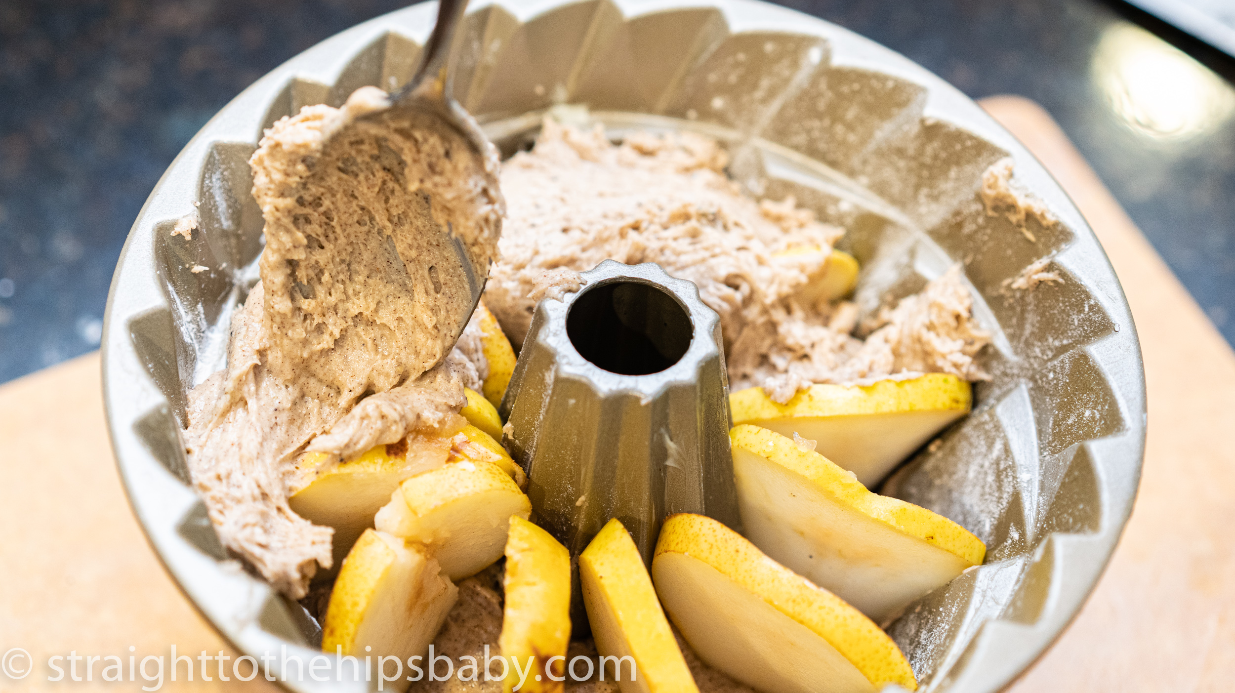 adding cake batter onto of the sliced pears in a fluted bundt pan