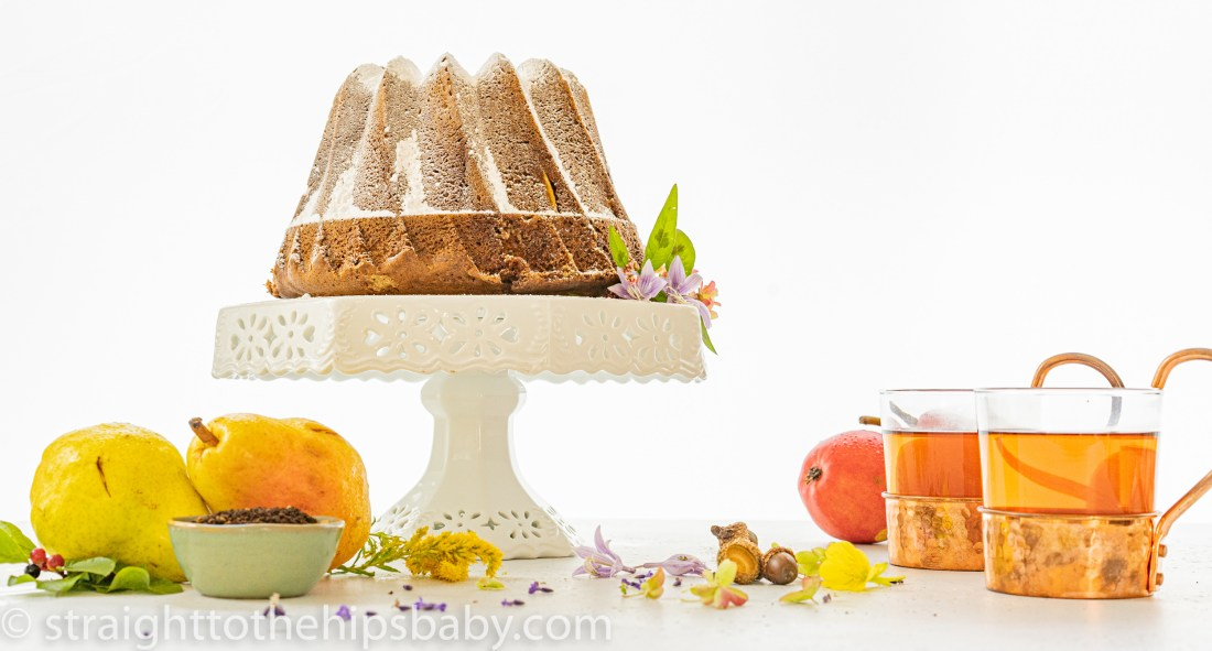 A delicious Bundt Cake on a white porcelain cake stand, surrounded by spices and fresh pears