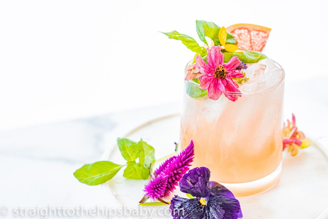 light pink grapefruit and gin cocktail in a double old fashioned glass with flower garnish