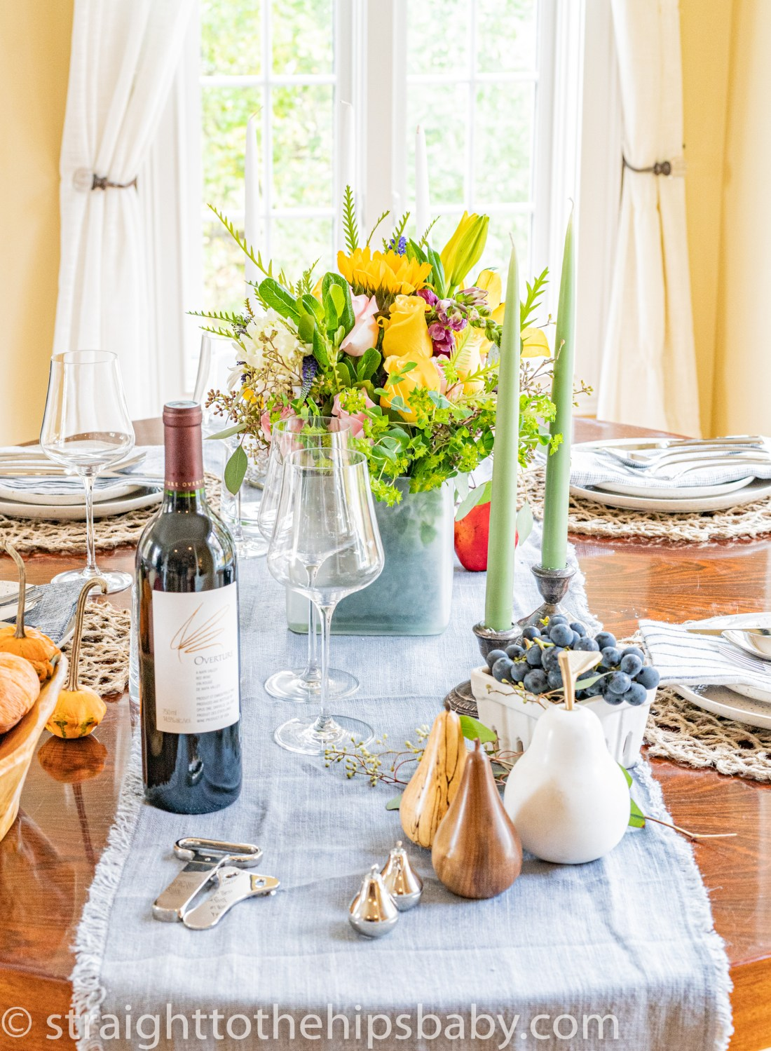 four place settings with a vibrant flower centerpiece, wine glasses, and tapered candles
