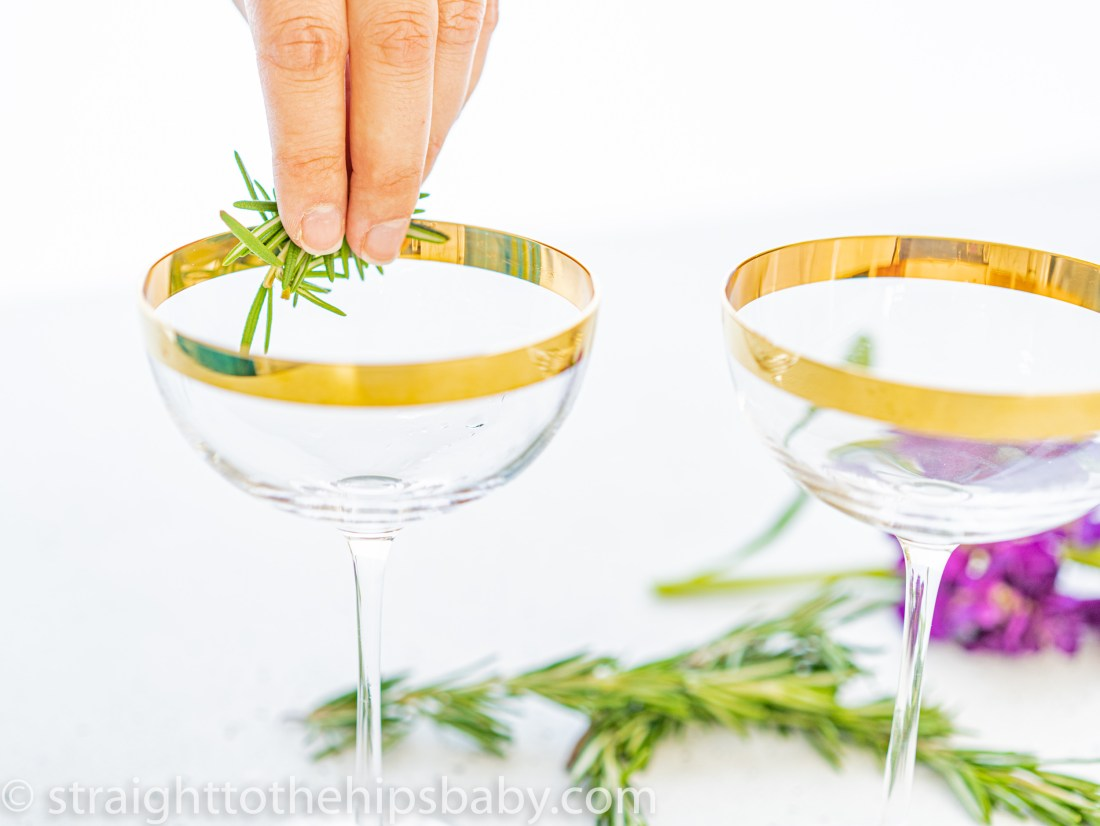 rubbing the edge of a coupe glass with fresh rosemary