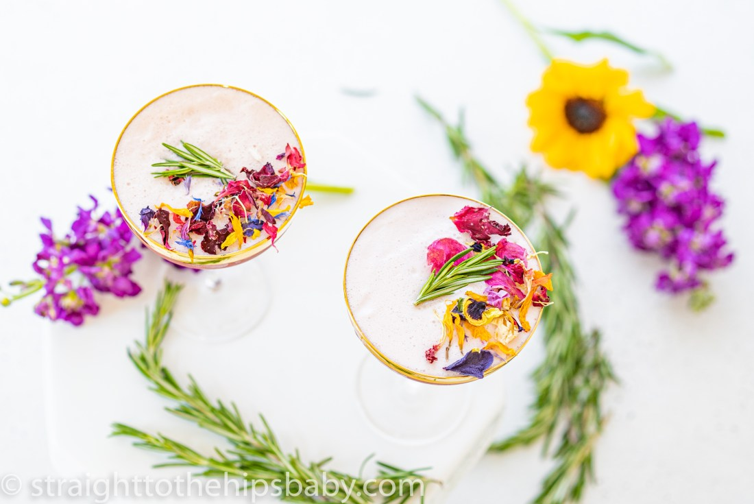 a top down view of two finished cocktails in coupe glasses, surrounded by flowers and rosemary